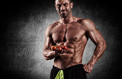 The very muscular sporty guy drinking protein in dark weight roo Royalty Free Stock Image