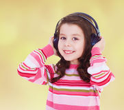 Very musical little girl listening to music. With your arms close to your ears.Concept of childhood and family values Royalty Free Stock Photo
