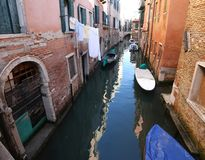 Very narrow navigable canal in Venice in Italy with boats. And italian houses Stock Photo