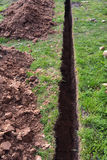 Very narrow trench in summer farm yard through grass. For water pipe Royalty Free Stock Image