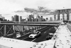 Manhattan from Brooklyn Bridge, New York with yellow taxi in the foreground - black and white version stock images