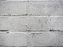 Painted white bricks wall with weathered layers of paint stock image