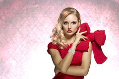 Very nice blond woman in red looking. Sophisticated lady in red dress with shining bracalet and elegant hair style looking in camera. keep the big bow Royalty Free Stock Images