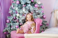 Very nice charming little girl blonde in pink dress sitting on a child`s armchair and laughs loudly  the background of Stock Image