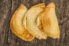 Very nice empanadas on wooden surface, perfect golden color and rustic elegant presentation, as seen from above Royalty Free Stock Image