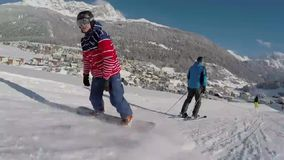 Snowboarders on slopes. A video of snowboarders coming down the slopes in a winter ski resort stock video footage