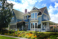 Very Nice Older Home. Street view of a beautiful large older luxurious blue country home with lots of gingerbread trim, a wide porch and a lot of windows Royalty Free Stock Image