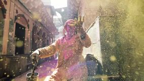 Holi Festival of Colors in India. Video clip of person in costume sat in street with bright sunlight reflecting off dust at Holi Festival of Colors in India