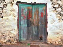A very old, ailing and with the most diverse paint residues provided wooden door with two wing doors royalty free stock photo