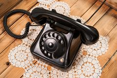 Old black phone on lace tablecloths and wooden background. Very Old black rotary phone with ring on lace tablecloths and wooden background. Close up Royalty Free Stock Photos