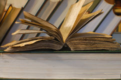 A very old book resting on book, more books in the background. Open old book in library, concept of knowledge Royalty Free Stock Photos