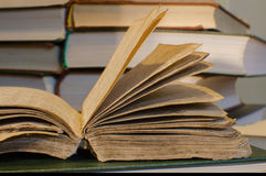 A very old book. Resting on book, more books in the background Royalty Free Stock Image