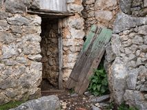 Very old broken weathered door made of wood. Stone house Island Cres, Croatia royalty free stock photo