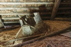 Very old and broken wooden tub lying in the barn attic on hay straw stock photos