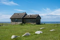 A very old building made of stone located on a green field near the ocean Stock Image