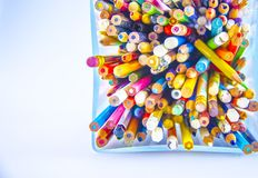 Colored pencils chaos. Very old colored crayons in a glass recipient Stock Photos