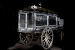 Very old and dusty hearse made of wood with large wooden wheels. Used to transport the coffin with the dead during the funeral in stock photos