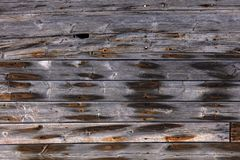 Exterior wooden wall with rusty nails. Very old exterior wall of an old building made of dry wooden boards of gray color with orange spots of rusty nails royalty free stock images