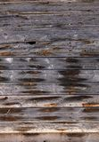 Old exterior wall made of wood. Very old exterior wall of an old building made of dry wooden boards of gray color with orange spots of rusty nails royalty free stock photos