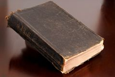 Very old family bible resting on table. Awash with warm light Royalty Free Stock Photography
