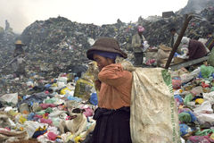 Very old Filipino woman working on landfill, dump. Philippines, Luzon, Baguio city: an elderly, a younger women and men are working among the garbage in the Royalty Free Stock Images