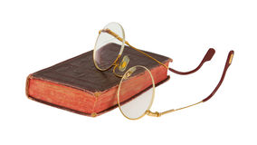 Very old glasses and a red book isolated. On white background Stock Photos