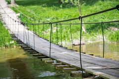 Very old hanging footbridge across river. Summer Stock Photography