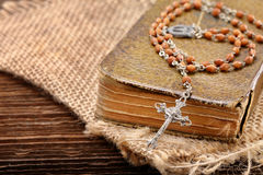 Very old holy bible and metal cross Stock Photos
