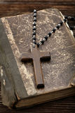 Very old holy bible and wooden cross Stock Photo