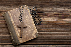 Very old holy bible and wooden cross Stock Photos