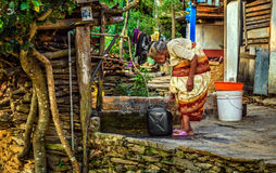 Very old hunched woman fills a jerrycan with water Stock Images