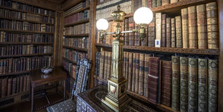 Very old library, 16th Century bookshelves with old fashioned light. 16th Century library room full of leather bound books royalty free stock image