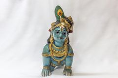 Very old little lord krishna doll with traditional oranments painted in blue colour placed in a white backdrop Stock Photography