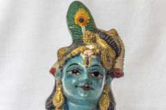 Very old little lord krishna doll with traditional ornaments painted in blue colour placed in a white backdrop Royalty Free Stock Image