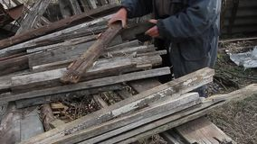 A very old man goes through the boards for repairing a hut or kindling fire, life after the war. A very old man goes over boards for repairing a hut or kindling stock video footage