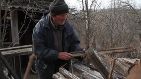 A very old man goes through the boards for repairing a hut or kindling fire, life after the war. A very old man goes over boards for repairing a hut or kindling stock footage