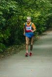 Very old man runs along the asphalt road Stock Photo