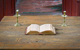 Very old open bible on table in medieval church Royalty Free Stock Photo