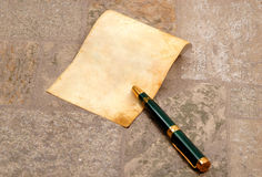 Very old paper with a pen. Very old paper with a vintage pen in a stone ( very textured stone Royalty Free Stock Image