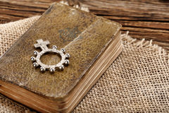 Very old prayer book and ten rosary on wooden background royalty free stock photo