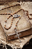 Very old prayer book and vintage rosary on wooden background Royalty Free Stock Photo