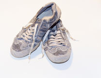 Very old running shoes with laces on a light background. Stock Photo