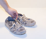 Very old running shoes with laces on a light background. Royalty Free Stock Photography