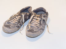 Very old running shoes with laces on a light background. Stock Photos