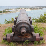 Very old rusted canon pointing at a bay Royalty Free Stock Photos