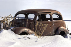 Very old rusted vintage car stuck in snow. Horizontal side view image of a very old antique car totally rusted and all windows broken with dead plants Stock Images