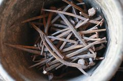 Very old rusty curved nails in the bucket royalty free stock images