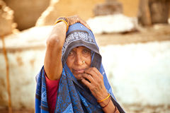 Very old and sad indian villager woman. With dark complexion sitting on stone branch looking at camera Royalty Free Stock Images