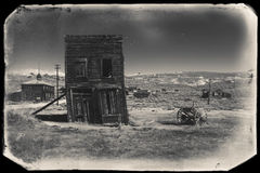 Very old sepia vintage photo with abandoned western building in the middle of a desert. Very old sepia vintage photo with abandoned and crooked western city Royalty Free Stock Photography