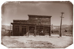 Very old sepia vintage photo with abandoned western saloon building in the middle of a desert stock image